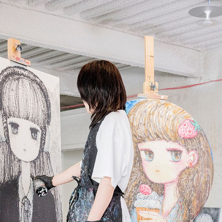 Stickymonger holding a spraypaint can up to a piece of artwork on an easel