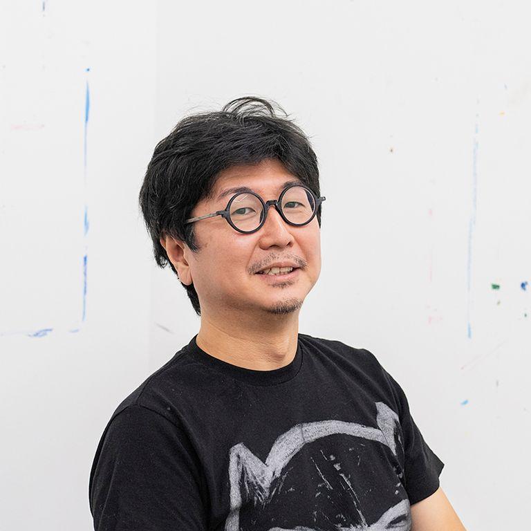 Susumu Kamijo in a black tshirt and glasses smiling