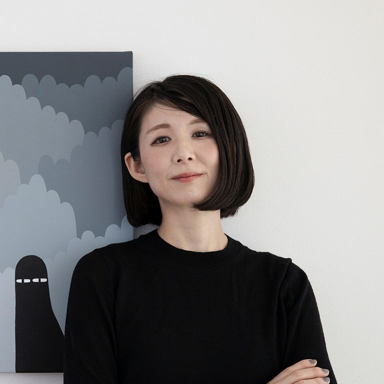 LY smiling standing in front of a greyscale painting