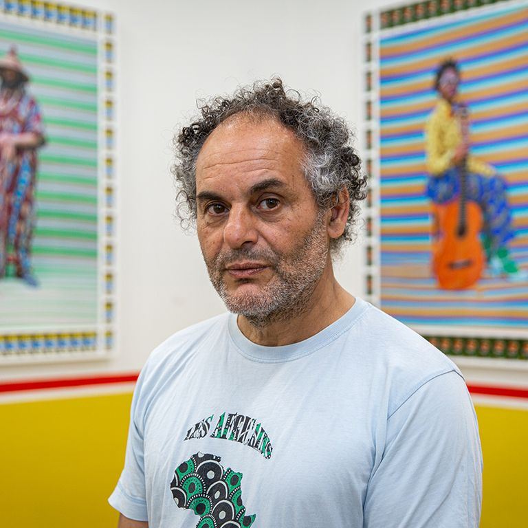 Hassan Hajjaj closeup portrait photo with two of his artworks blurred behind him