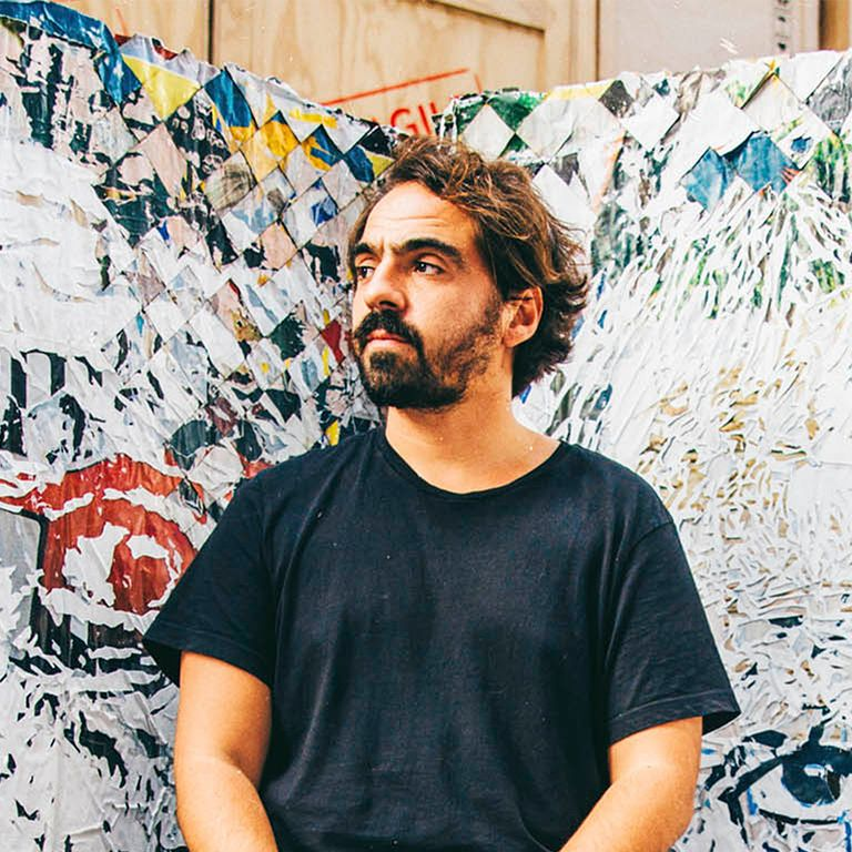 Vhils standing in front of a mixed media artwork as he glances to the side