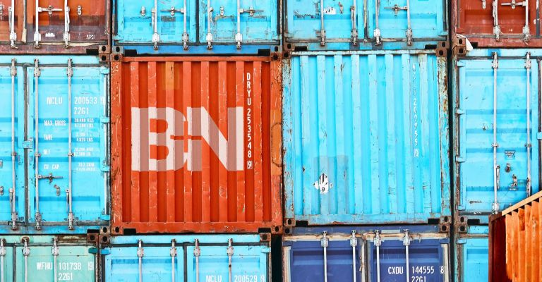 Side view of different stacked colorful shipping containers with the B+N logo printed in white on an orange one.