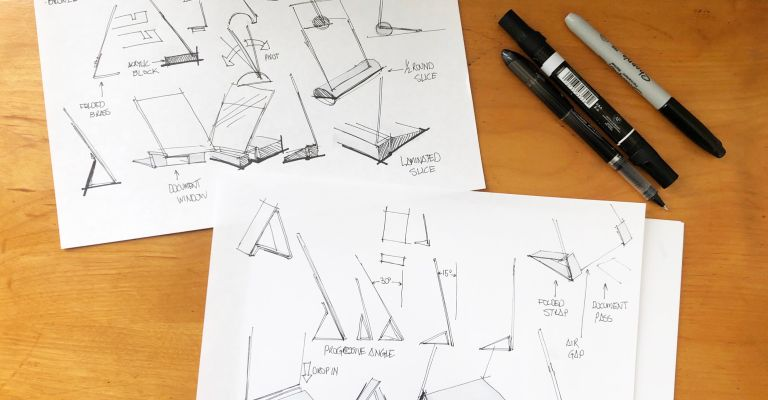 Different architectural sketches on paper are laid across a wooden table with some pens showing on the top right.