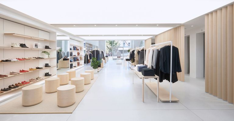 Interior view of Evelane's shop. A white space is decorated with wooden seats and tables with wooden System 1224 shelves lining against the left wall to display pairs of shoes.