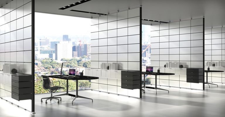 A view of an officespace with white panels separating each space. Black and gray desks and chairs sit in each space with white System 1224 shelves holding cabinets and books along the panels.