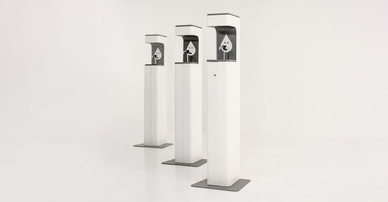 Three white tall sanitizing stations are lined up diagonally, the one on the right being the closest and left farthest.