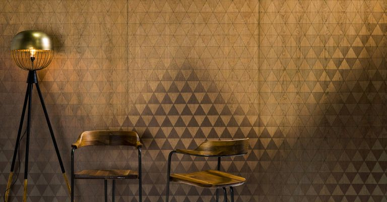 Two wooden chairs and a golden lamp are placed on the floor in front of a golden triangle patterned Infused Veneer wall.