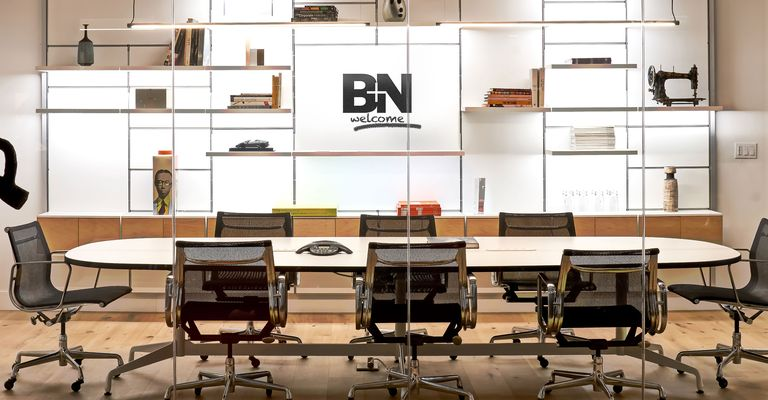 """The B+N Logo as well as the word """"welcome"""" are printed in black against a white wall utilizing white System 1224 shelves carrying miscellaneous items. A long office desk is placed on the floor surrounded by chairs."""