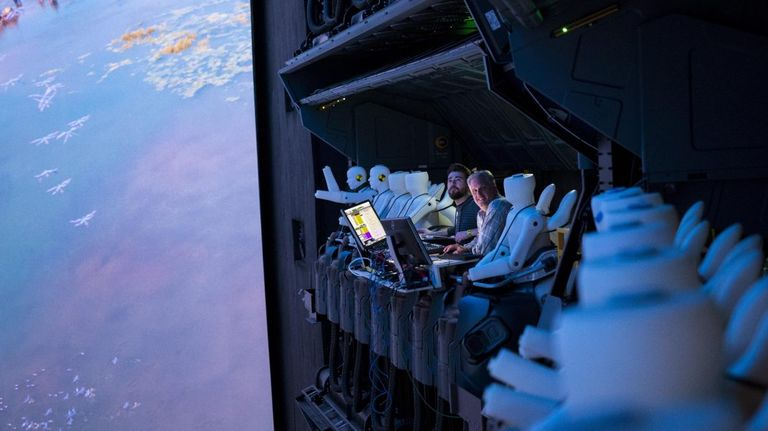 Two Disney ride programmers sit in the Flight of Passage ride seats