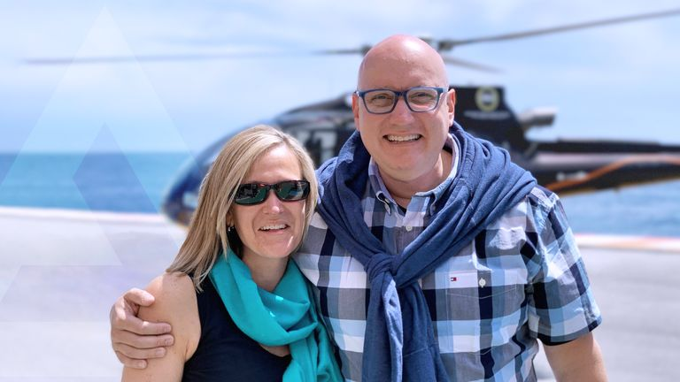 Brian Llyod standing with his partner in front of a helicopter