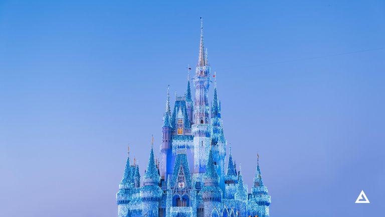 A Disney castle lit up in dazzling blue Christmas lights