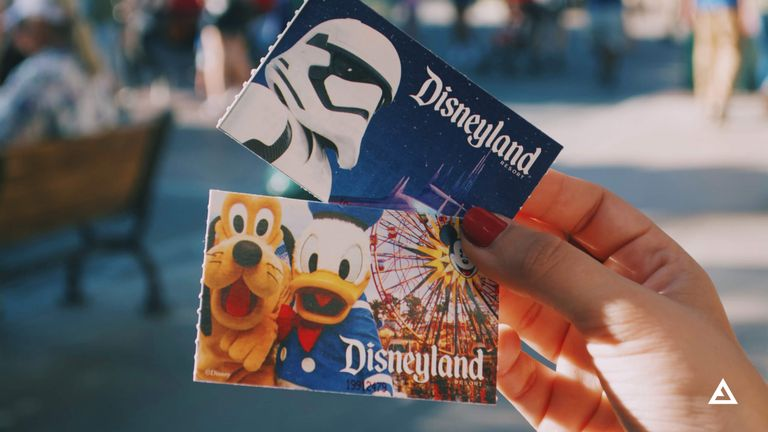 A hand holds a pair of Disneyland Park tickets