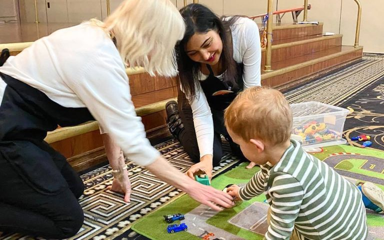 Women helping a child during play time