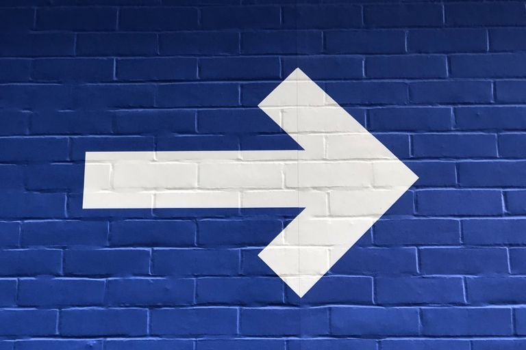 A white arrow pointing right painted on a blue brick wall