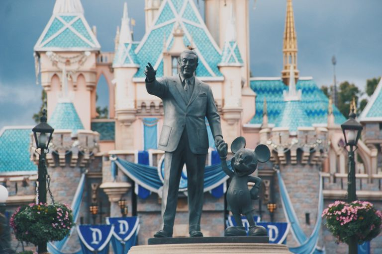 A statue of Walt Disney and Mickey Mouse in front of the Disney castle