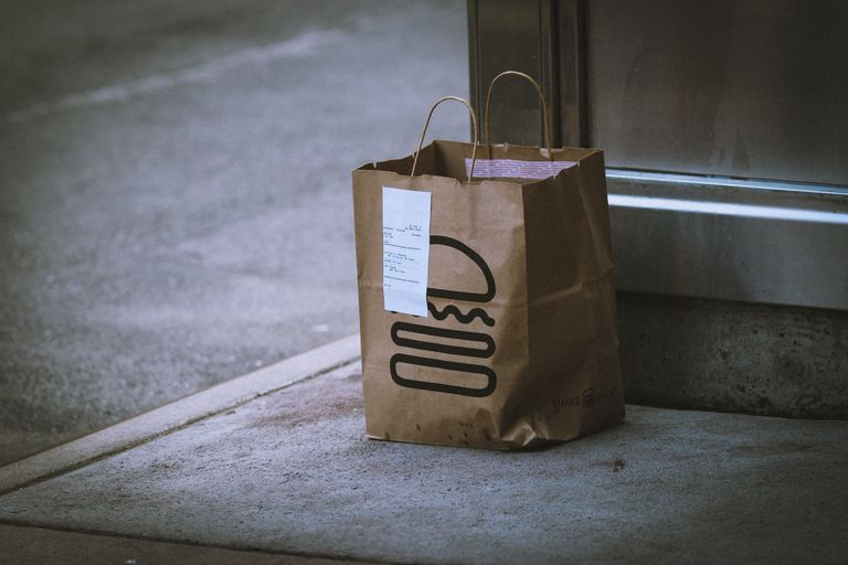 A brown paper delivery bag at a doorstep