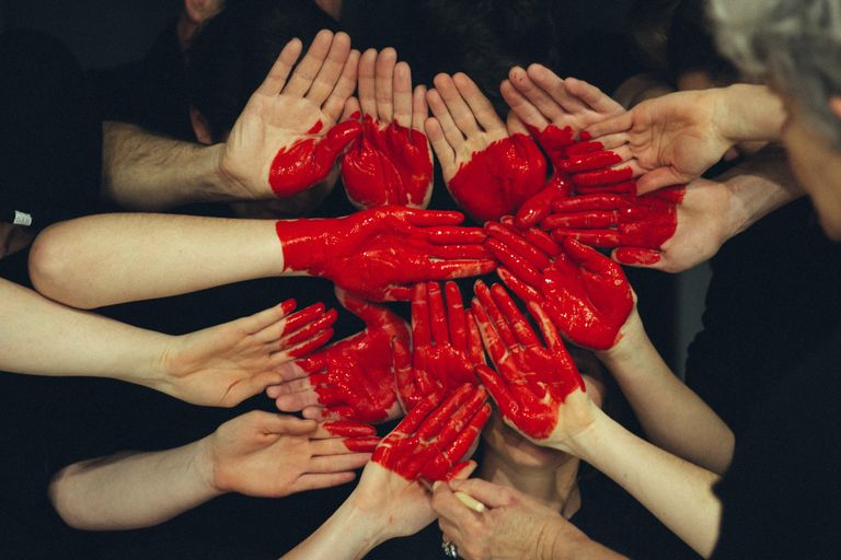 Many hands raised with a heart symbol painted on the palms with red paint