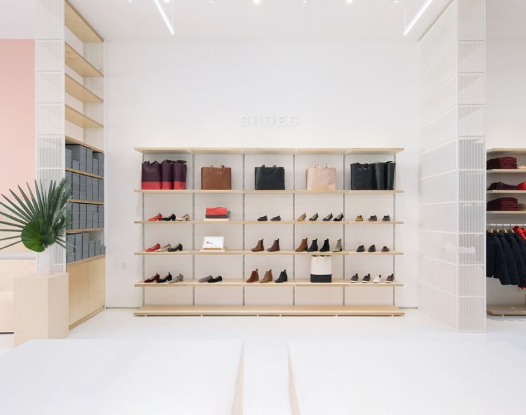 Wooden System 1224 shelves along a white wall are used to display various shoes and purses on sale.