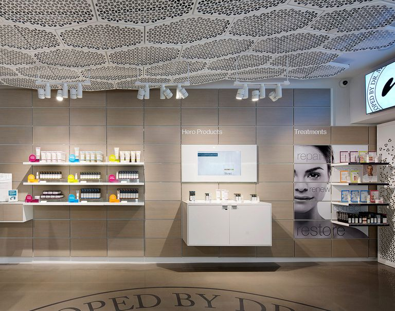 Interior of a beauty store. Various beauty products are lined up along white shelves against a beige wall.