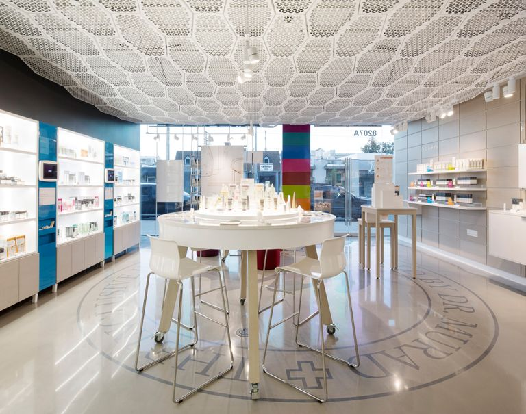 Interior of the Murad shop with a set of white chairs and a table centered in the middle. The walls are lined with white System 1224 shelves showcasing various skincare products.