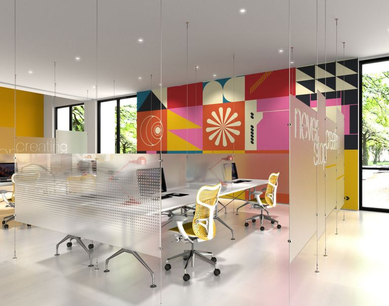 A colorfully decorated office space is divided up with frosted glass panels held up by thin metallic cables and rods. Within the spaces are desks with monitors and yellow rolling chairs.