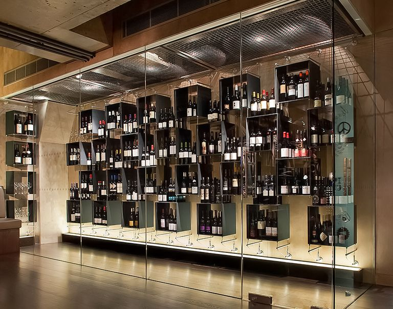View of a large glass display showcasing a variety of wines held up on square black shelves through Cables and Rods.
