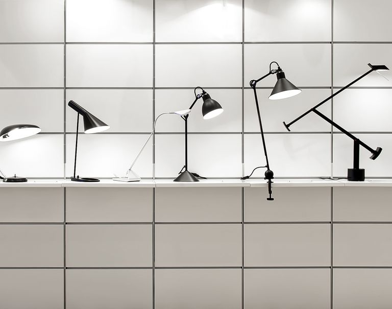 Various black lamps are lined up along a white shelf held up against a grid patterned wall.