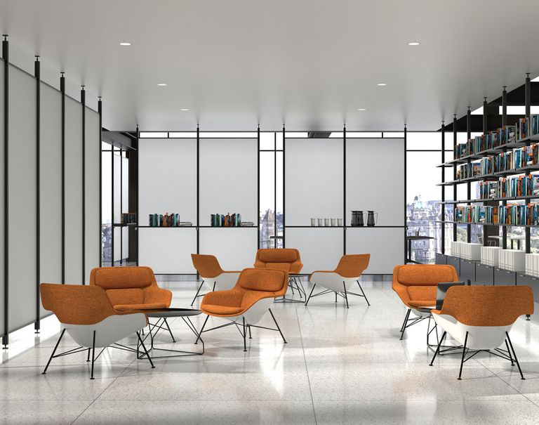 Interior of a white office space. Orange chairs and round tables are placed along the floor with white paneled Sorbetti fixtures blocking off the space.