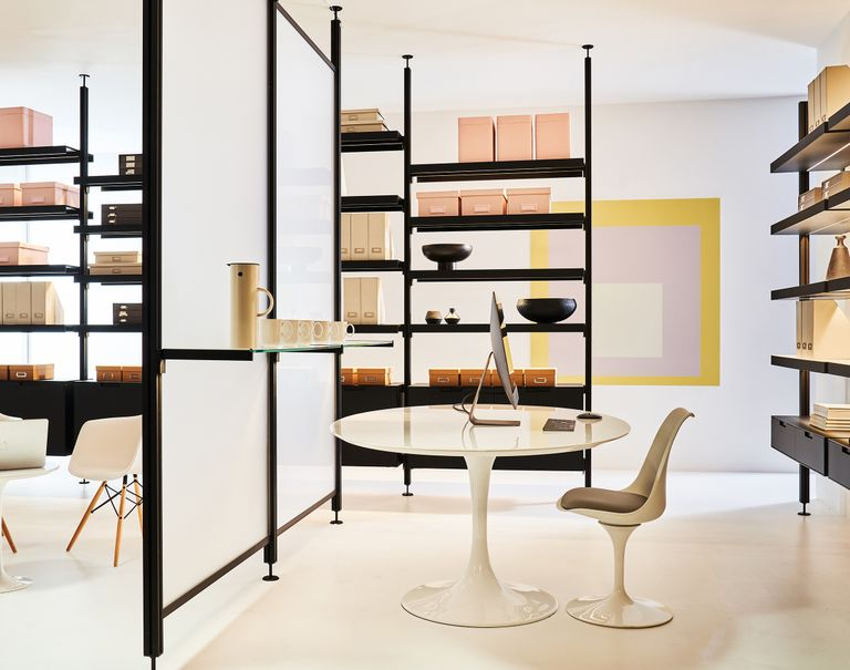 Black Sorbetti shelves are used to carry miscellaneous office boxes and decorations around an office space. Two white Sorbetti with white panels are used along the center to divide the room.