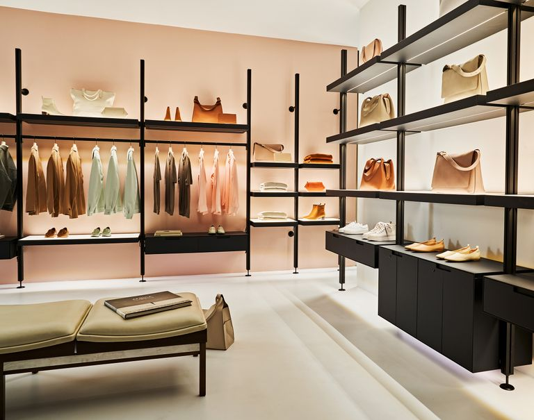 Lit black Sorbetti shelves are lined against the walls of a retail store. The system shelves various bags and shoes on display as well as clothes hung on the racks.