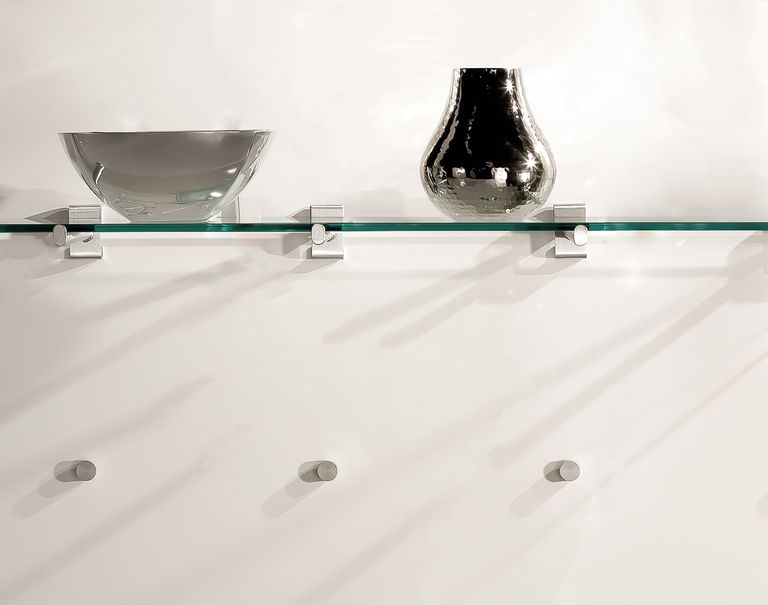A glass shelf displaying a metal bowl and vase is propped up using the Puck System against a white wall.