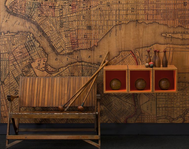 A wooden bench and shelves holding various wooden sports equipment are propped against a wall decorated in a map patterned Infused Veneer.