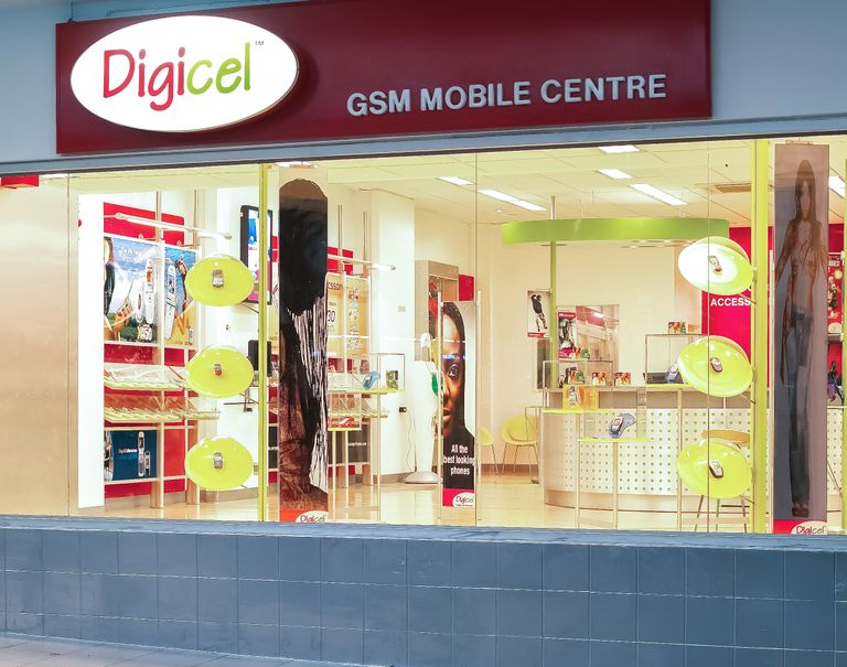 Exterior of a Digicel store's entrance. The Digicel logo is lit up above glass windows showing the interior of the store.