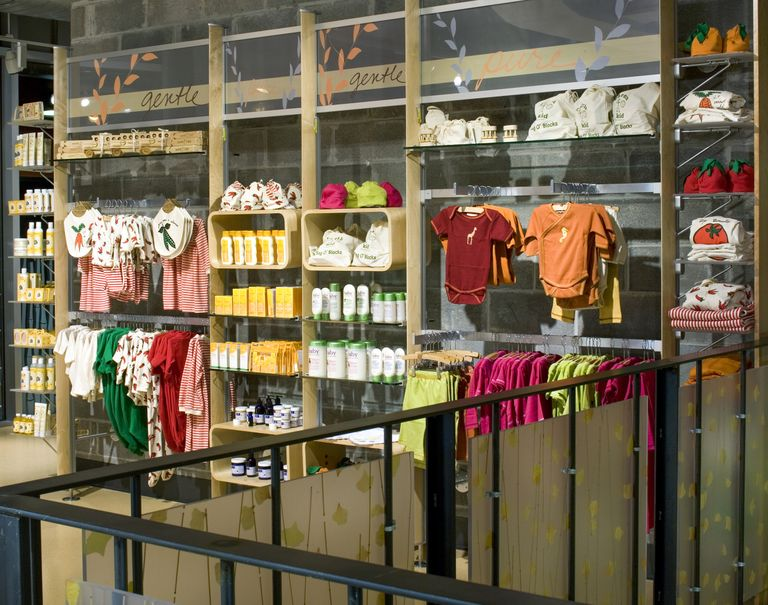 Various baby clothes and products are hung up on display on wooden shelves and metal racks.
