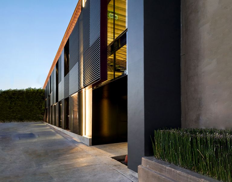Diagonal view of a sleek yellow lit black building with tall glass windows and black Fortina panels running horizontally against them.