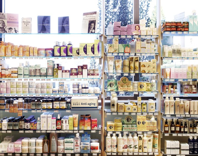 Many different beauty products are placed along a series of glass shelves against a bright window.