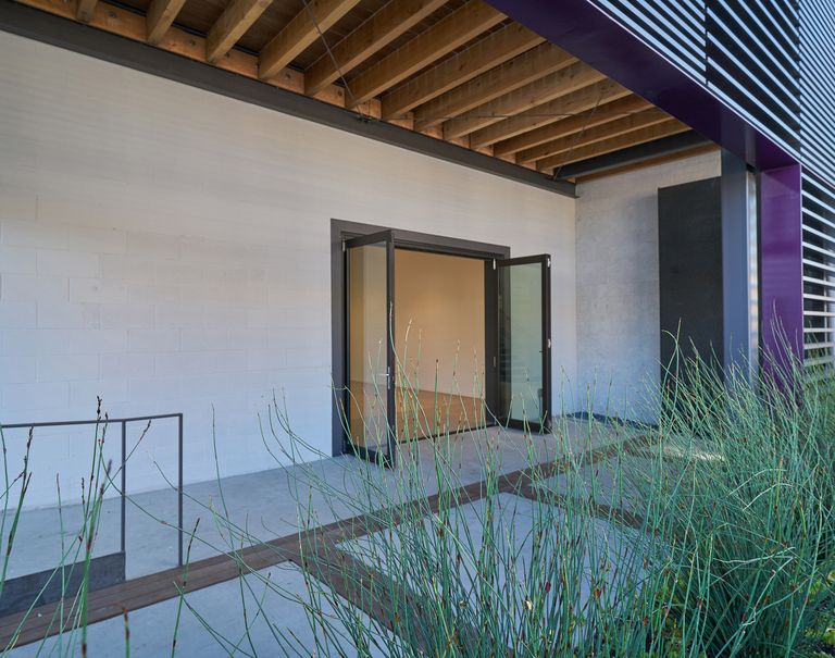 Open glass doors reveal the interior view of a building. On the front sides of the building, black Fortina panels run horizontally with purple panels bordering the edges of them.