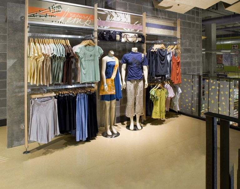 Clothing items are hung up on display on wooden and metal racks. Two mannequins wearing clothes are placed in the center.