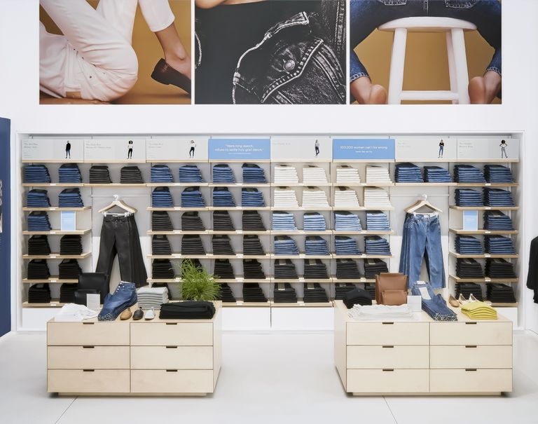 Various clothing items, mainly jeans, are neatly folded and on display within wooden shelves against a wall.
