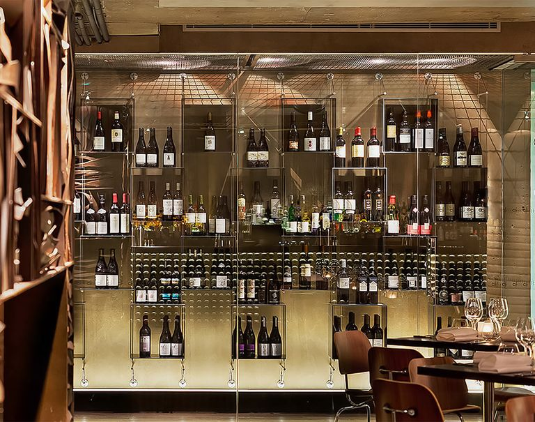 Front facing view of a large glass display showcasing a variety of wines held up on shelves through Cables and Rods.