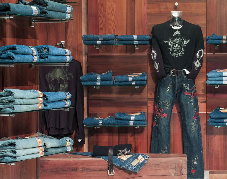 Jeans are placed on display on shelves held up by the Puck System on wooden walls.
