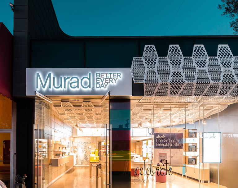 Entrance of Murad's shop with open glass doors and glass windows. The Murad logo is printed largely over the doors on top of metal, with metal embellishments on the side.
