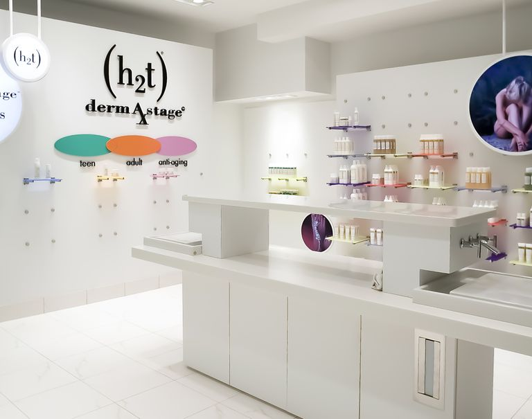 Interior of a white store. White walls using metal puck fixtures prop up colorful shelves displaying bottles.