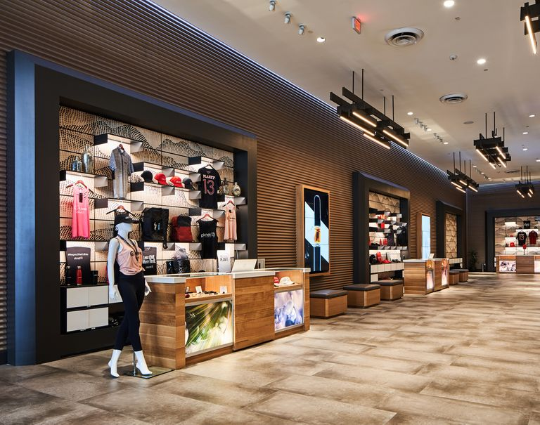 A view of the interior of Planet 13. Dot patterned Veneer panels lined with System 1224 shelves are lined against the walls showcasing a variety of different Planet 13 merchandise.