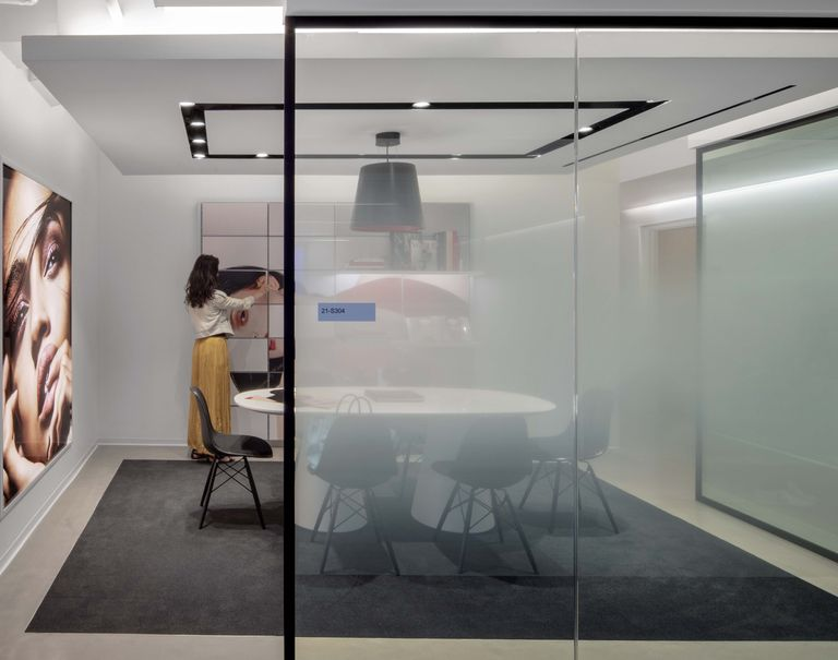 View of a room surrounded with frosted glass, on the side there's a woman standing in front of a panel with a printed image of a woman laying on her side.