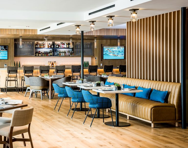 Interior of the Griffin Club. Wooden Fortina panels are used to divide a bar decorated with tables, stools, and couches.
