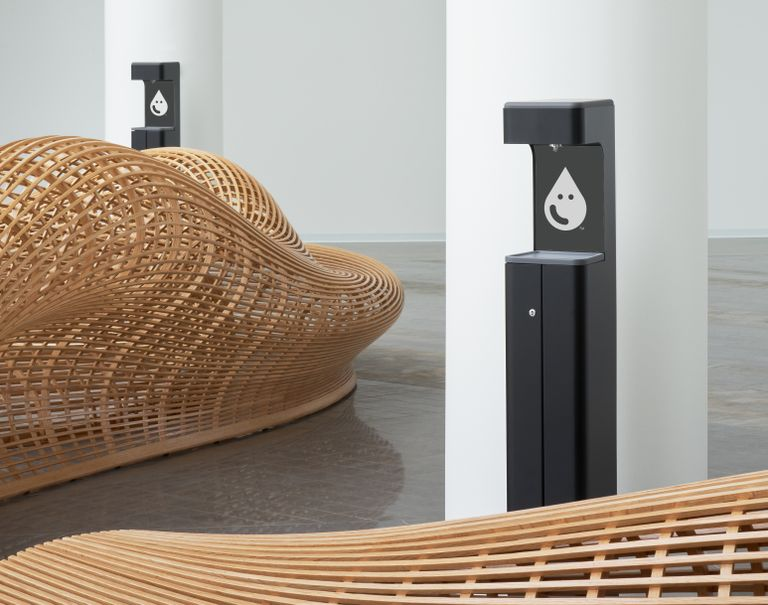 Two black tall Hand Sanitizer structures are placed in front of white cylindrical columns. Also placed in the room are two wooden woven artistic pieces.