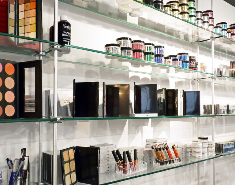Various makeup products are lined up neatly along glass shelves held up by metal cables and rods.