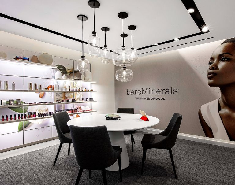 """A white round table with black chairs sits at the center of a room with the left wall decorated with an image of a woman along with text reading """"bareMinerals The Power of Good"""" and the other wall displaying various beauty products on white shelves."""