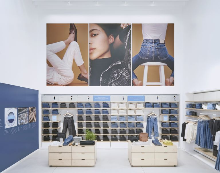 Series of images of a model posing in denim clothes are hung above wooden System 1224 shelves showcasing various neatly folded jeans. Wooden cabinets also displaying clothing articles stand in front of the shelves.